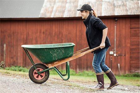 farmhand (female) - Side view of female farmer pushing wheelbarrow on rural road Stock Photo - Premium Royalty-Free, Code: 698-07439563