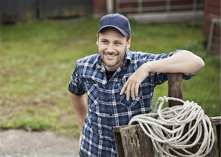 Smiling farmer looking away while leaning on railing at farm Stock Photo - Premium Royalty-Free, Code: 698-07439574