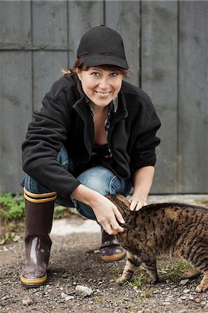 farmhand (female) - Full length portrait of female farmer petting cat against barn Stock Photo - Premium Royalty-Free, Code: 698-07439570