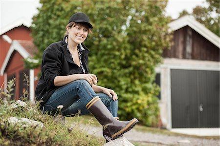 farmhand (female) - Full length portrait of confident female farmer sitting on rock at farm Stock Photo - Premium Royalty-Free, Code: 698-07439571