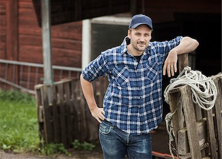 Portrait of confident farmer leaning on railing Stock Photo - Premium Royalty-Free, Code: 698-07439572