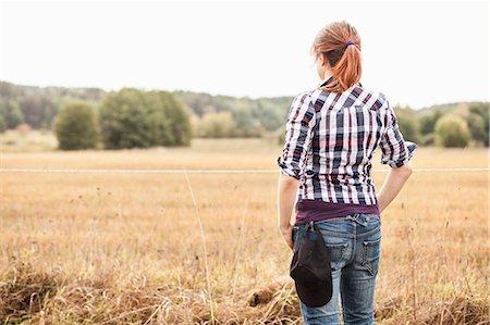 farmhand (female) - Rear view of female farmer standing at field Stock Photo - Premium Royalty-Free, Code: 698-07439584