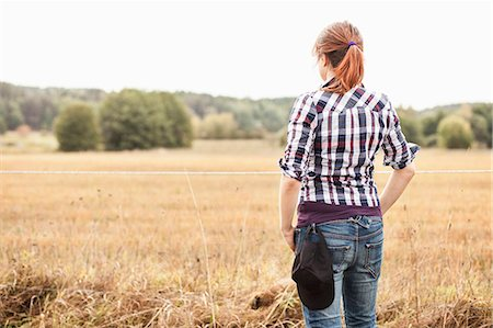 farmhand (female) - Rear view of female farmer standing at field Stock Photo - Premium Royalty-Free, Code: 698-07439584