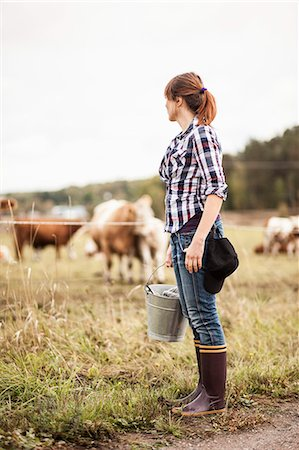 farmhand (female) - Female farmer with bucket standing on field with animals grazing in background Stock Photo - Premium Royalty-Free, Code: 698-07439586