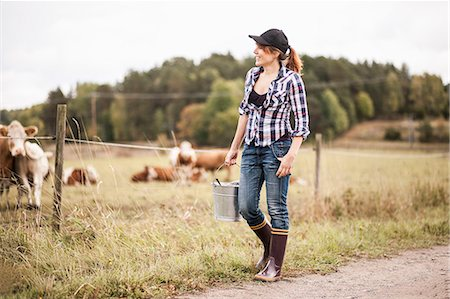 farmhand (female) - Female farmer with bucket walking while animals grazing in field Stock Photo - Premium Royalty-Free, Code: 698-07439587