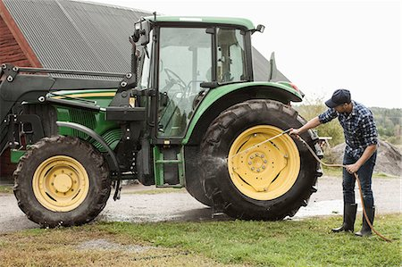 Full length farmer washing tractor wheel with hose in farm Stock Photo - Premium Royalty-Free, Code: 698-07439582