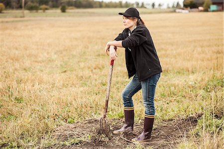 farmhand (female) - Full length of thoughtful woman with pitchfork standing at field Stock Photo - Premium Royalty-Free, Code: 698-07439594