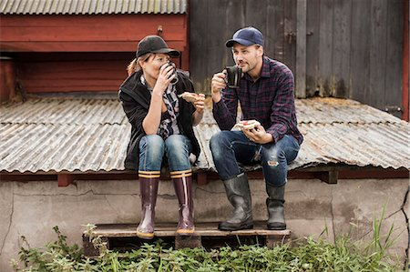 Full length of couple having breakfast on corrugated iron at farm Stock Photo - Premium Royalty-Free, Code: 698-07439601