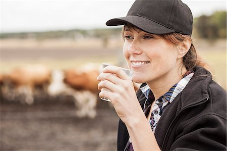 farmhand (female) - Mid adult female farmer drinking milk in farm Stock Photo - Premium Royalty-Free, Code: 698-07439602