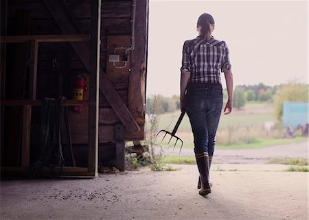 farmhand (female) - Rear view of female farmer with pitchfork walking in barn Stock Photo - Premium Royalty-Free, Code: 698-07439611