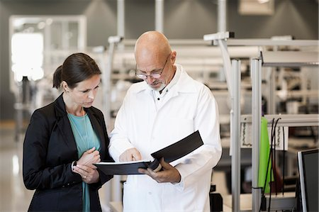 sold sign - Male engineer and businesswoman looking at file in industry Stock Photo - Premium Royalty-Free, Code: 698-07439635