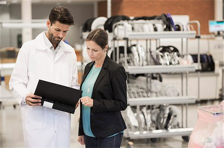 sold sign - Businesswoman and engineer looking at file in manufacturing plant Stock Photo - Premium Royalty-Free, Code: 698-07439636