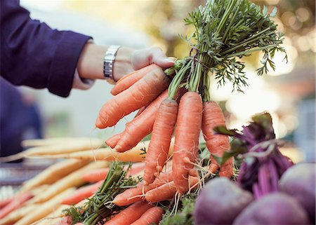 Cropped image of woman buying carrots at market stall Stock Photo - Premium Royalty-Free, Code: 698-07439638