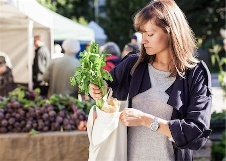 Young woman buying leaf vegetables at market Stock Photo - Premium Royalty-Free, Code: 698-07439646