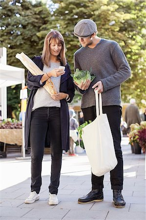 Full length of couple using mobile phone while shopping vegetables in market Stock Photo - Premium Royalty-Free, Code: 698-07439648