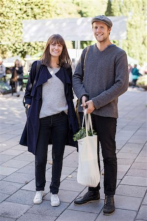 Full length of couple with groceries bag on sidewalk Stock Photo - Premium Royalty-Free, Code: 698-07439654