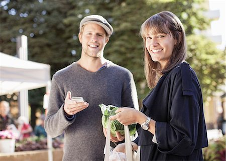 Portrait of smiling couple with mobile phone and groceries in market Stock Photo - Premium Royalty-Free, Code: 698-07439650