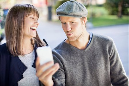 stockholm - Happy couple photographing themselves through mobile phone outdoors Stock Photo - Premium Royalty-Free, Code: 698-07439667