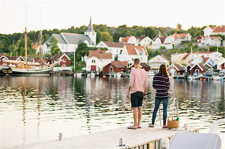 Full length rear view of couple fishing on pier at lake Stock Photo - Premium Royalty-Free, Code: 698-07439686