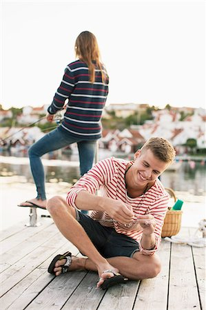 Happy man adjusting fishing rod while woman fishing in background at pier Stock Photo - Premium Royalty-Free, Code: 698-07439688