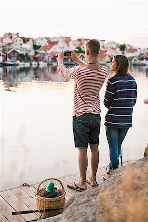 Rear view of couple photographing view through mobile phone by lake Stock Photo - Premium Royalty-Free, Code: 698-07439689