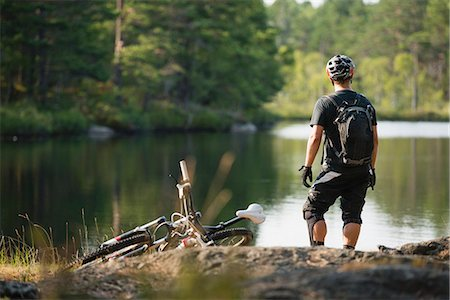 Rear view of mountain biker looking at lake Stock Photo - Premium Royalty-Free, Code: 698-07439696