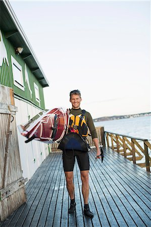 Full length portrait of happy man carrying kayak on shoulder at boathouse Stock Photo - Premium Royalty-Free, Code: 698-07439704