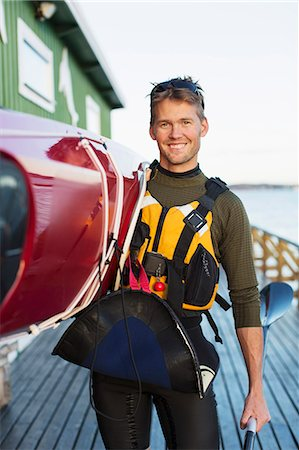 Portrait of confident man carrying kayak on shoulder at boathouse Stock Photo - Premium Royalty-Free, Code: 698-07439703