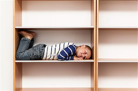 Full length of playful boy lying in empty shelf at home Stock Photo - Premium Royalty-Free, Code: 698-07439737