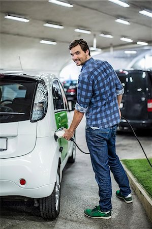 Full length portrait of young man charging electric car at gas station Stock Photo - Premium Royalty-Free, Code: 698-07439752