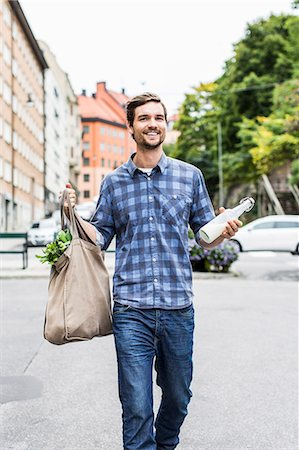 Full length portrait of happy man with groceries walking on street Stock Photo - Premium Royalty-Free, Code: 698-07439777