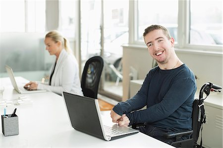 Portrait of happy businessman with cerebral palsy using laptop in office Stock Photo - Premium Royalty-Free, Code: 698-07439778