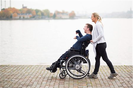 Caretaker pushing disabled man on wheelchair along lake Stock Photo - Premium Royalty-Free, Code: 698-07439785