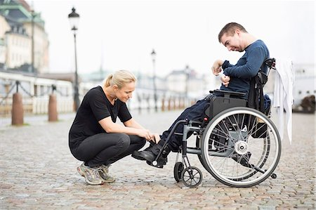 Female caretaker putting on disabled man's shoes on street Stock Photo - Premium Royalty-Free, Code: 698-07439787