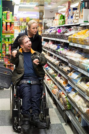 Disabled man on wheelchair shopping with caretaker in supermarket Stock Photo - Premium Royalty-Free, Code: 698-07439789