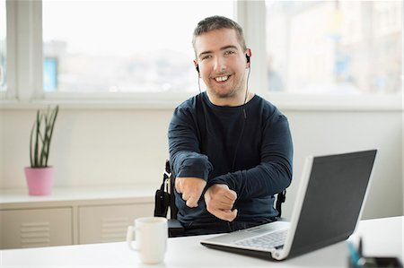 Portrait of happy disabled businessman with laptop at desk in office Stock Photo - Premium Royalty-Free, Code: 698-07439780