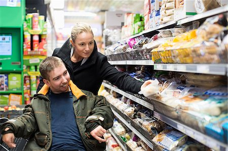 Caretaker shopping with disabled man on wheelchair in supermarket Stock Photo - Premium Royalty-Free, Code: 698-07439790