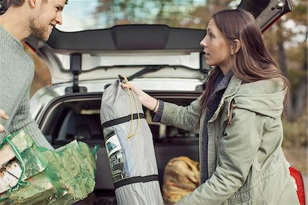 Side view of couple holding camping equipment against car Stock Photo - Premium Royalty-Free, Code: 698-07587727