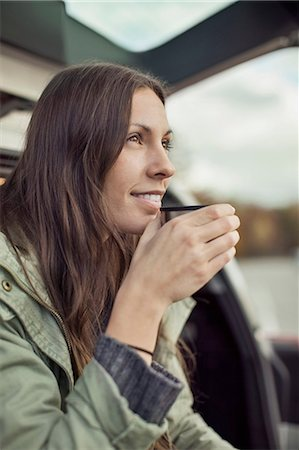 Young woman looking away while drinking coffee at car's trunk Stock Photo - Premium Royalty-Free, Code: 698-07587730