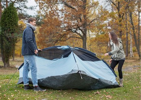 Full length of young couple pitching tent in forest Stock Photo - Premium Royalty-Free, Code: 698-07587764