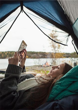 Side view of young woman using digital tablet in tent Stock Photo - Premium Royalty-Free, Code: 698-07587778