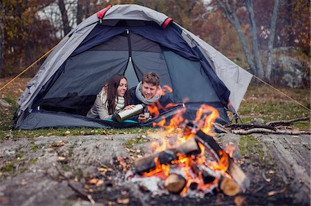 fall - Woman pouring coffee for man while lying in tent at forest Stock Photo - Premium Royalty-Free, Code: 698-07587773