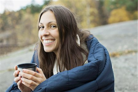 Portrait of happy woman wrapped in blanket holding coffee cup while camping Stock Photo - Premium Royalty-Free, Code: 698-07587784