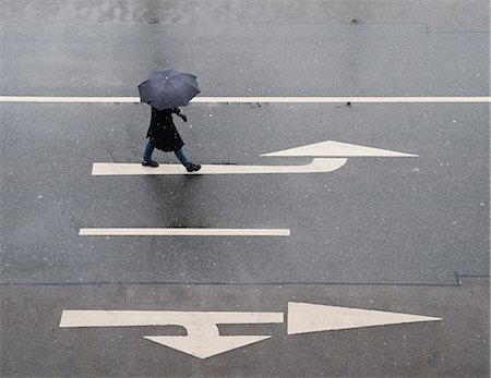 people with umbrellas in the rain - High angle view of woman with umbrella walking on road Stock Photo - Premium Royalty-Free, Code: 698-07587795