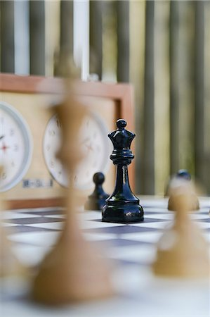 Selective focus of queen facing off king on a chess board Stock Photo - Premium Royalty-Free, Code: 698-07587800