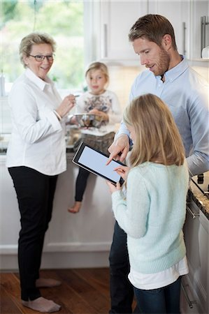 sister - Family using digital tablet while cooking in kitchen Stock Photo - Premium Royalty-Free, Code: 698-07587836