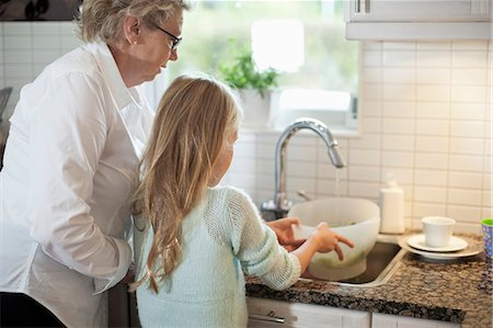 Grandmother and granddaughter washing vegetables in kitchen Stock Photo - Premium Royalty-Free, Code: 698-07587838