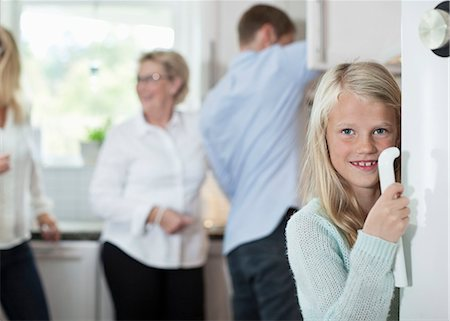 Portrait of smiling girl holding door handle with family in background at kitchen Stock Photo - Premium Royalty-Free, Code: 698-07587831