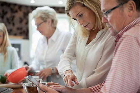 Woman using digital tablet with father-in-law while cooking in kitchen Stock Photo - Premium Royalty-Free, Code: 698-07587848