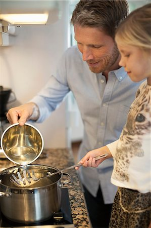 stove - Father and daughter cooking in kitchen Stock Photo - Premium Royalty-Free, Code: 698-07587840